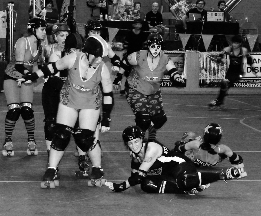 Risky? These women compete in a roller derby where they skate, block and score on a concrete floor. There is risk—in the sense of loss or injury.